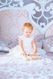 白色礼服的愉快的小女孩在圣诞节装饰的屋子打开礼物 图库摄影