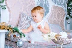 白色礼服的愉快的小女孩在圣诞节装饰的屋子装饰树 免版税库存照片