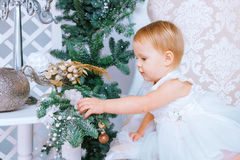 白色礼服的愉快的小女孩在圣诞节装饰的屋子装饰树 免版税库存图片