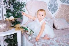 白色礼服的愉快的小女孩在圣诞节装饰的屋子装饰树 免版税图库摄影