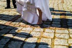 白色礼服的愉快的新娘没有鞋子在老石头p站起来 免版税库存图片