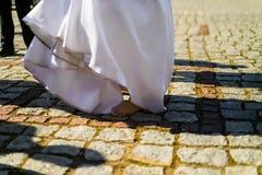 白色礼服的愉快的新娘没有鞋子在老石头p站起来 库存图片