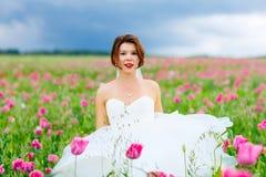 白色礼服的愉快的新娘获得乐趣在花鸦片领域 免版税库存照片