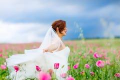 白色礼服的愉快的新娘获得乐趣在花鸦片领域 免版税库存图片