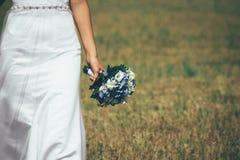 白色礼服的新娘是在与花束的领域 免版税图库摄影
