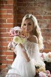 白色礼服的新娘有卷发的嗅花束的 免版税库存图片