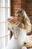 白色礼服的新娘有卷发的嗅花束的 图库摄影