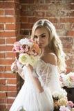白色礼服的新娘有卷发的嗅花束的 免版税库存照片