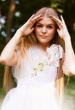 白色礼服的有趣的白肤金发的妇女 库存图片
