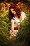 白色礼服的深色的白种人妇女在红色和黄色花的公园在拿着花的夏天日落坐gr 免版税库存图片