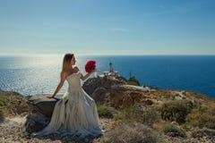 白色礼服的美丽的妇女在石头 库存照片