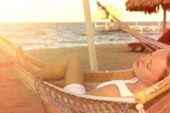 白色礼服的美丽的妇女在晴朗的海滩的吊床 库存照片