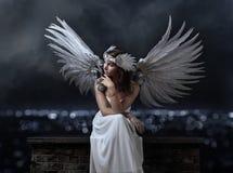 白色礼服的美丽的妇女有天使的在背景飞过 免版税库存图片