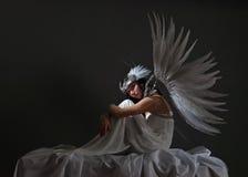 白色礼服的美丽的妇女有天使的飞过 免版税库存图片