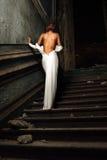 白色礼服的美丽的妇女有赤裸后面的在宫殿。 库存照片