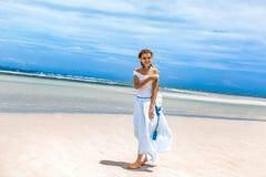 白色礼服的美丽的年轻时髦的女人走由的 免版税图库摄影