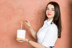 白色礼服的美丽的年轻深色的女孩拿着有胶浆的,蜡,糖一个瓶子 秀丽产业 免版税库存图片