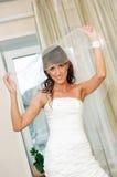 白色礼服的美丽的微笑新娘打开新娘面纱 库存图片