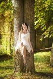 白色礼服的美丽的愉快的女孩坐树 免版税库存图片