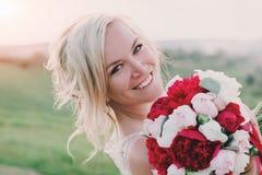 白色礼服的美丽的愉快的白肤金发的妇女微笑在太阳光的 焕发太阳 库存图片