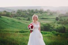 白色礼服的美丽的愉快的白肤金发的妇女微笑在太阳光的 焕发太阳 免版税图库摄影