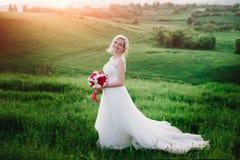 白色礼服的美丽的愉快的白肤金发的妇女微笑在太阳光的 焕发太阳 库存照片