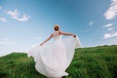 白色礼服的美丽的愉快的白肤金发的妇女微笑在太阳光的 焕发太阳 免版税库存图片