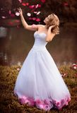 白色礼服的美丽的新娘有桃红色和红色花的,公园 免版税库存图片