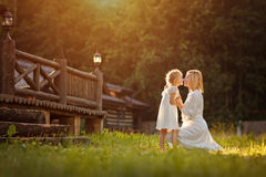 白色礼服的美丽的母亲金发碧眼的女人轻轻地拥抱一女孩kneeli 库存照片