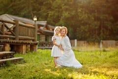 白色礼服的美丽的母亲金发碧眼的女人轻轻地拥抱一女孩kneeli 库存图片