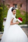 白色礼服的美丽的深色的新娘有玫瑰花束posi的 免版税库存图片