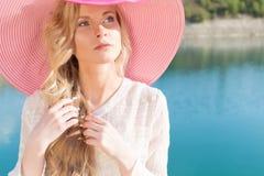 白色礼服的美丽的甜柔和的女孩在蓝色海的岸的轻的大桃红色帽子日落夏天晚上太阳的 库存照片