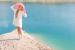 白色礼服的美丽的甜柔和的女孩在蓝色海的岸的轻的大桃红色帽子日落夏天晚上太阳的 免版税库存图片