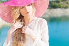 白色礼服的美丽的甜柔和的女孩在蓝色海的岸的轻的大桃红色帽子日落夏天晚上太阳的 免版税库存照片