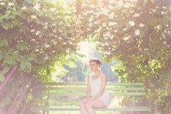 白色礼服的美丽的精美端庄的妇女在他的头的新娘有头发的和冠状头饰在一个繁茂花园里坐长凳下 免版税库存照片