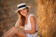 白色礼服的美丽的苗条女孩在一个干草堆附近坐与 免版税库存照片