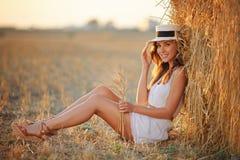 白色礼服的美丽的苗条女孩在一个干草堆附近坐与 库存图片