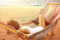 白色礼服的美丽的被日光照射了妇女在海滩的吊床 图库摄影