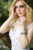 白色礼服的美丽的年轻新娘有在树附近的花束的在夏天绿色公园 库存照片