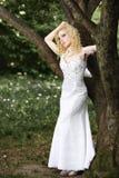 白色礼服的美丽的年轻新娘有在树附近的花束的在夏天绿色公园 免版税库存图片