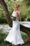 白色礼服的美丽的年轻新娘有在树附近的花束的在夏天绿色公园 免版税库存照片