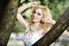 白色礼服的美丽的年轻新娘有在树附近的花束的在夏天绿色公园 图库摄影