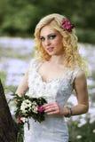 白色礼服的美丽的年轻新娘有花束的在夏天绿色公园 免版税图库摄影