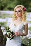 白色礼服的美丽的年轻新娘有花束的在夏天绿色公园 免版税库存图片