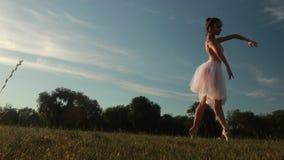 白色礼服的芭蕾舞女演员在草坪背景和蓝天跳舞在晚上 股票视频