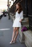 白色礼服的逗人喜爱的女孩和郁金香美丽的花束。 免版税图库摄影
