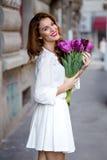 白色礼服的逗人喜爱的女孩和郁金香美丽的花束。 免版税库存照片