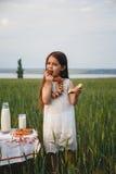 白色礼服的逗人喜爱的微笑的小女孩吃百吉卷用在绿色领域,夏令时的牛奶的 库存图片