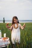 白色礼服的逗人喜爱的微笑的小女孩用百吉卷和牛奶在绿色领域,夏令时 库存照片