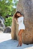 白色礼服的逗人喜爱的相当被晒黑的亭亭玉立的女孩在海滩 免版税库存照片
